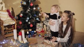 De kleine jongen met zijn zuster pakt de doos van de Nieuwjaar` s gift dichtbij de prachtig verfraaide Kerstboom uit Het jonge ge stock footage