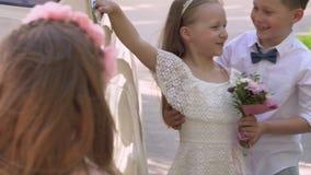 De kleine jongen om de zuster bij de grote retro auto te omhelzen stock footage