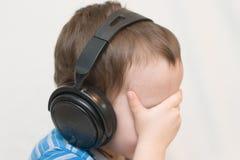 De kleine jongen in oortelefoons royalty-vrije stock fotografie