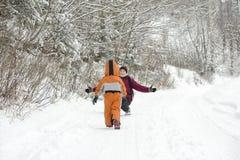 De kleine jongen in overall die de sneeuw naar de moeder doornemen De winterdag in de naald bos Achtermening stock afbeeldingen