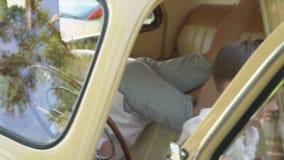De kleine jongen overweegt op voorwaartse zitting een wiel en een venster in de retro auto stock videobeelden