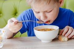 De kleine jongen is smakelijk etend een heerlijke soep stock foto