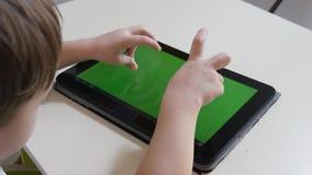 De kleine jongen speelt op de tablet Het groene scherm Mening van hierboven stock videobeelden