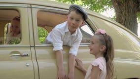 De kleine jongen stelt voor de foto bij de retro auto met de zuster stock videobeelden