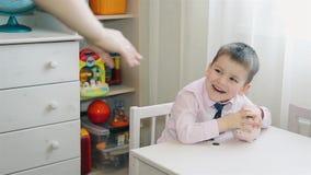 De kleine jongen telt het geaccumuleerde geld in het spaarvarken stock video