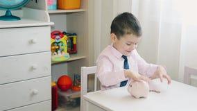 De kleine jongen telt het geaccumuleerde geld in het spaarvarken stock videobeelden