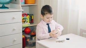 De kleine jongen telt het geld in het spaarvarken stock videobeelden