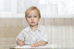 De kleine jongen trekt zijn aandacht royalty-vrije stock afbeelding