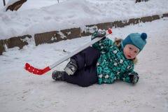 De kleine jongen werd vermoeid van het spelen van hockey en ging op de sneeuw met een stok rusten in de winter in een park royalty-vrije stock fotografie
