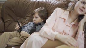 De kleine jongen zit op de bank met afstandsbediening en de jonge zuster zit dichtbij en spreekt aan mobiele telefoon stock videobeelden