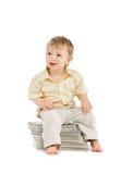 De kleine jongen zit op een stapel van boeken Royalty-vrije Stock Afbeeldingen