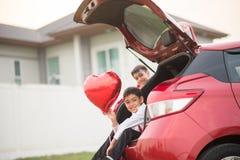 De kleine jongens die op de achterdeur van de auto met ballonhart zitten overhandigen royalty-vrije stock foto