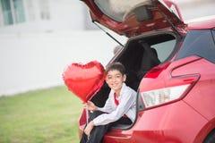 De kleine jongens die op de achterdeur van de auto met ballonhart zitten overhandigen stock foto