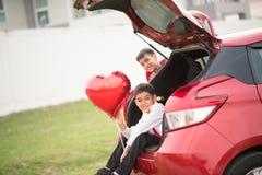 De kleine jongens die op de achterdeur van de auto met ballonhart zitten overhandigen stock afbeelding