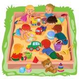 De kleine jongens en de meisjes die in de zandbak zitten, spelen hun speelgoed Stock Afbeeldingen