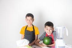 De kleine jongens mengen het sap van de watermeloen door mixer te gebruiken stock foto