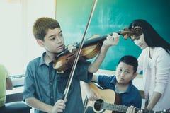De kleine jongens spelen en de praktijkviool in de ruimte van de muziekklasse stock foto's