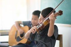 De kleine jongens spelen en de praktijkviool in de ruimte van de muziekklasse stock fotografie