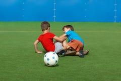 De kleine jongens verschuiven op voetbalgebied Royalty-vrije Stock Fotografie