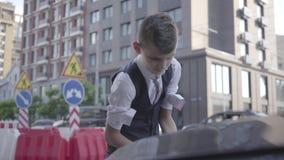 De kleine jongensop een hoger niveau weergevens de kokers en de verhogingen de kap van de auto Zekere jongen de auto gaan bevesti stock video