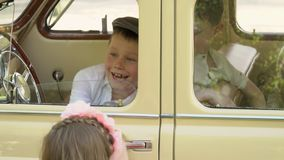 De kleine jongensspelen met de bouwstijl in de grote retro auto stock video