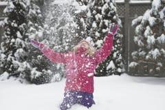 De kleine Kaukasische blonde meisjes in rood jasje speelt met sneeuw op de achtergrond van het sparrenonduidelijke beeld royalty-vrije stock afbeelding