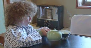 De kleine Kaukasische jongen die yukata dragen giet thee in Japan