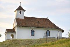 De Kleine kerk bovenop een groene heuvel Stock Foto