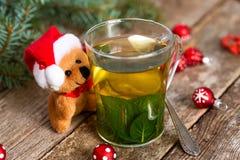 De kleine Kerstman draagt omhelzend een kop van hete muntthee stock fotografie