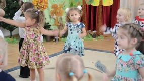 De kleine kinderen dansen en zingen het lied Ochtendprestaties in kleuterschool stock footage