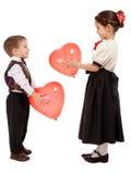 De kleine kinderen geven elkaar rode ballons Stock Afbeeldingen