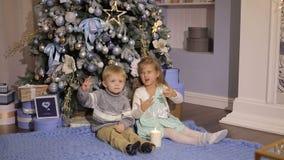 De kleine kinderen maken wens dichtbij de Kerstboom stock footage