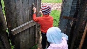 De kleine kinderen openen de oude houten deur gaan voor een gang op aard, langzame motie