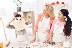 De kleine kleinkinderen voor de gek houden rond in keuken met hun grootmoeder royalty-vrije stock afbeeldingen