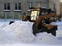De kleine lader harkt gevallen sneeuw Royalty-vrije Stock Afbeelding