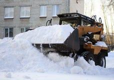 De kleine lader harkt gevallen sneeuw Stock Afbeeldingen