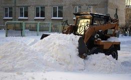 De kleine lader harkt gevallen sneeuw Royalty-vrije Stock Foto