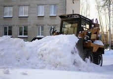 De kleine lader harkt gevallen sneeuw Stock Afbeelding