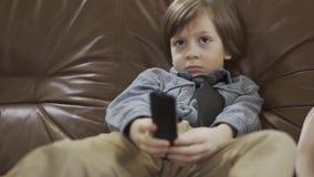 De kleine leuke jongenszitting op de leerbank met benen die apart kanalen bij TV-ver gebruiken veranderen Leuk kind binnen stock videobeelden