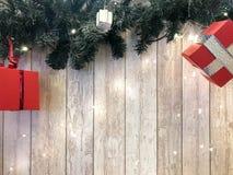 De kleine leuke rode feestelijke giftdozen, Kerstmis, de decoratie van het Nieuwjaar op de achtergrond van groene Kerstboom verta royalty-vrije stock foto