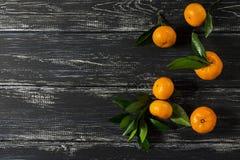 De kleine mandarijnen met groene bladeren op een zwarte houten oppervlakte Royalty-vrije Stock Foto's