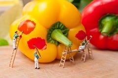 De kleine mensen schilderen peper aan een andere kleur Het concept groepswerk en het koken Stock Afbeeldingen