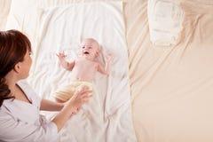 De kleine moeder die van de jongensbaby massagehanden en benen doen royalty-vrije stock foto