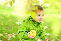 De kleine mooie jongen loopt op een groene open plek met een appel stock afbeelding