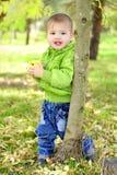 De kleine mooie jongen loopt op een groene open plek met een appel royalty-vrije stock foto
