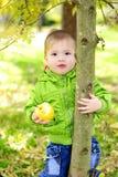 De kleine mooie jongen loopt op een groene open plek met een appel stock foto