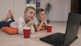 De kleine mooie jongens die op de vloer op oranje decoratieve hoofdkussens liggen eten heerlijke popcorn en letten op het interes stock footage