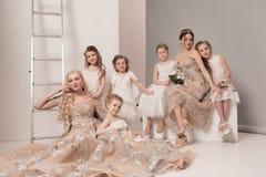 De kleine mooie meisjes met bloemen kleedden zich in huwelijkskleding Stock Foto