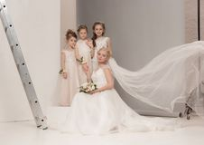De kleine mooie meisjes met bloemen kleedden zich in huwelijkskleding Royalty-vrije Stock Afbeeldingen
