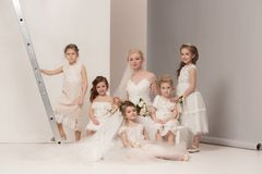 De kleine mooie meisjes met bloemen kleedden zich in huwelijkskleding Stock Afbeelding